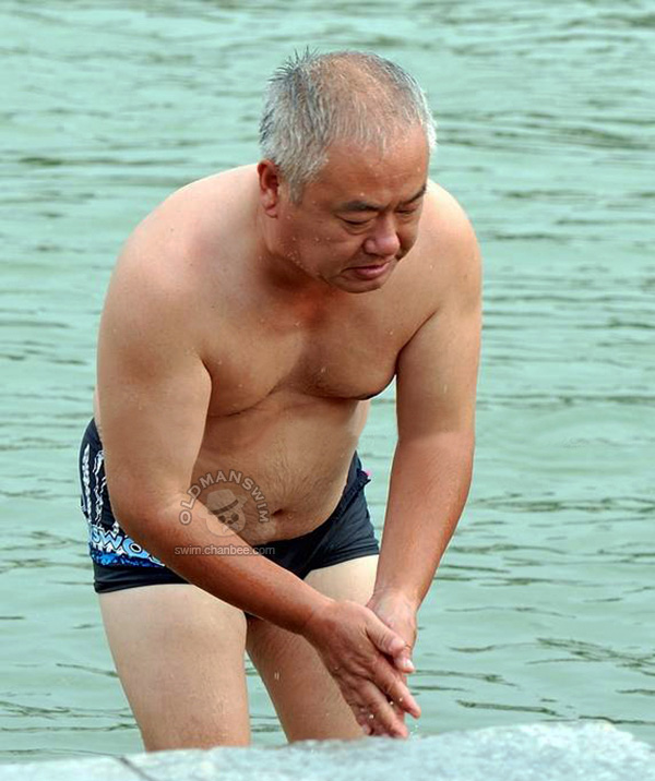 White hair swimming old man in a black swimsuit out of water