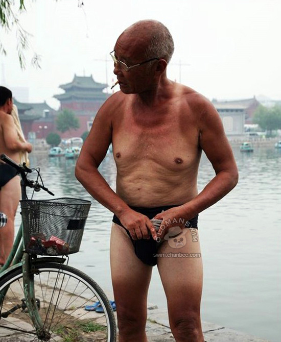 Swimming old man in a black underwear wipeing his body