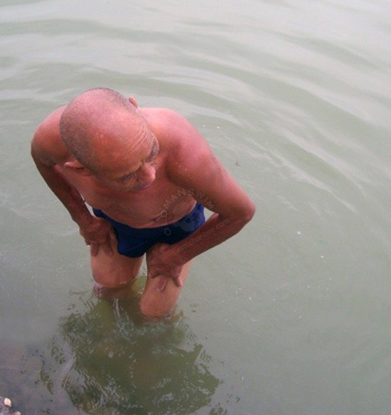 Bald thin old man in a blue underwear bathing by lake
