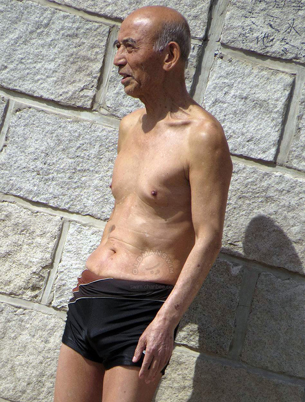 Thin swimming old man in a black underwear by river - JPOLD