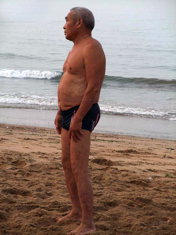Swimming old daddy in black pants on beach