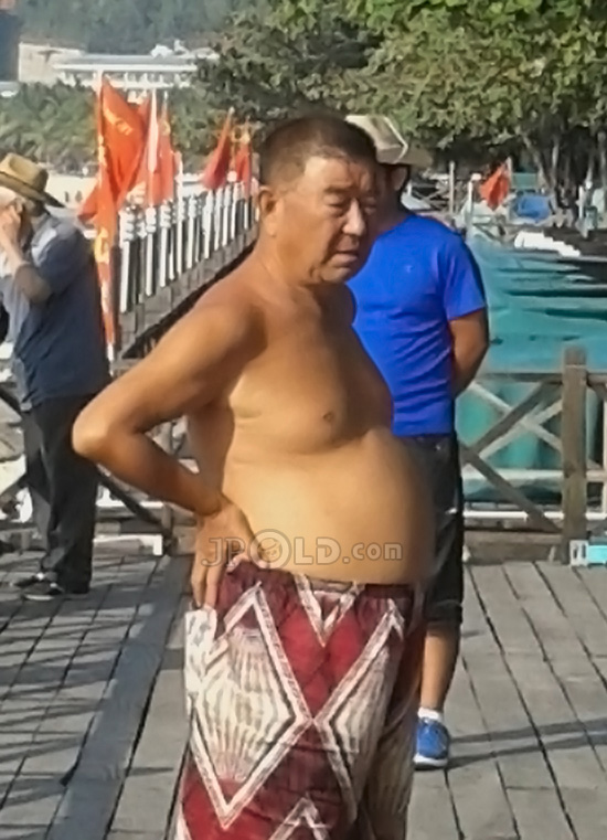 Belly old daddy in a figure pants on the beach
