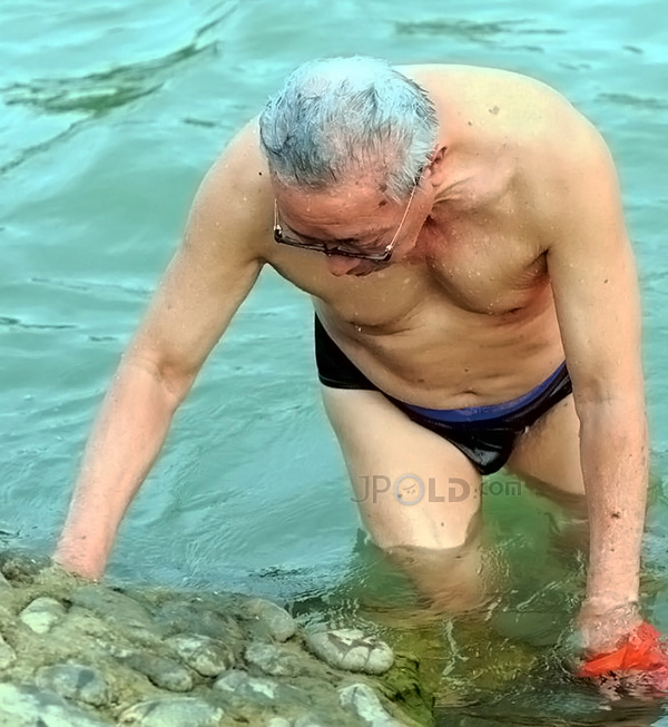 White hair glasses old man in a black underwear out of water
