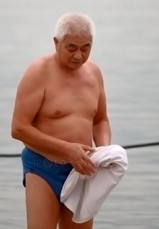 White hair swimming old man in blue underwear standing by river