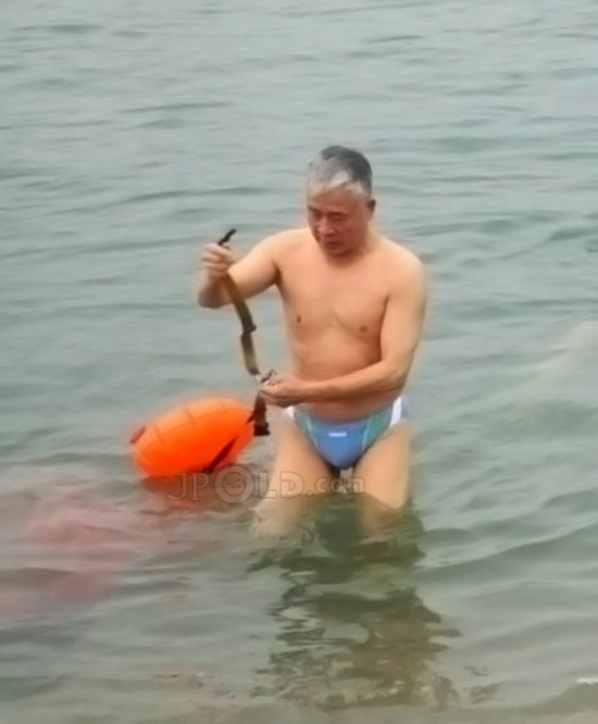 Swimming grandpa in a stripe underwear out of water