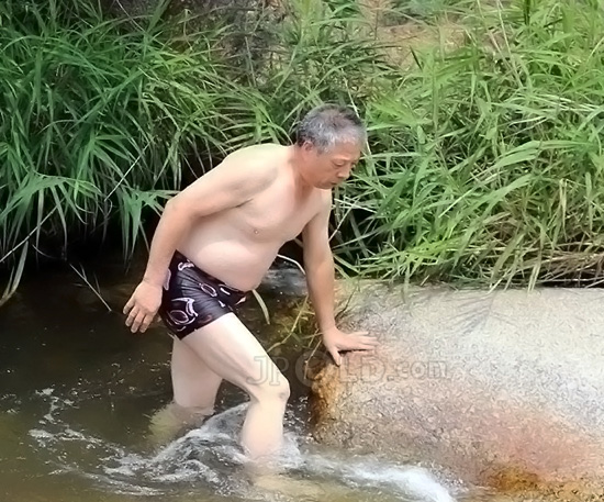 Old daddy in black underwear swimming in valley pool