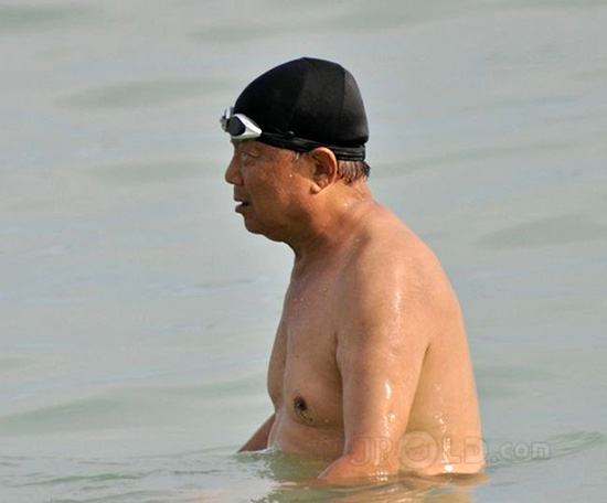 Fat swimming old man in black swimsuits out of water