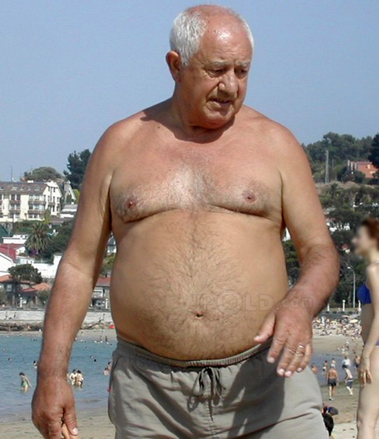 White hair belly grandpa in grey pants at the sea