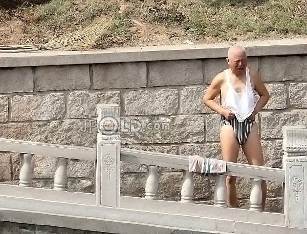 Short white hair old man in striped underwear by the river