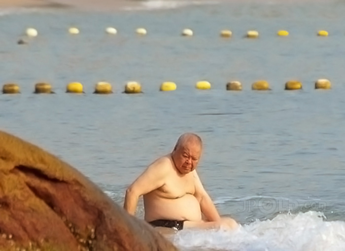 Fat swimming old man in black underwear lying on the beach