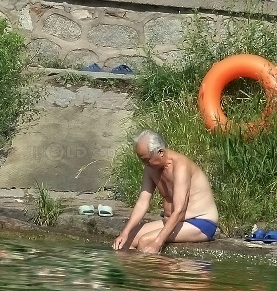 White hair grandpa in blue underwear by the lake
