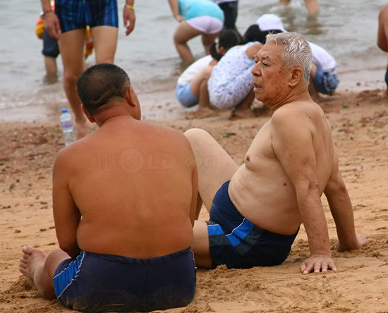 Tourist old men in underwear sitting on beach