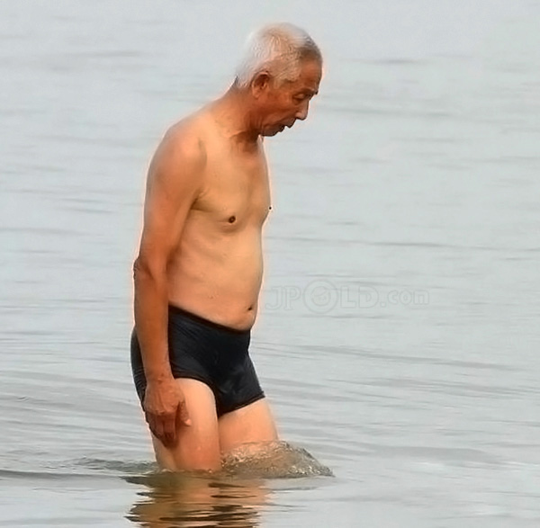 Old man in black swimming trunks out of water
