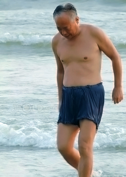 Swimming old man in blue underwear out of water
