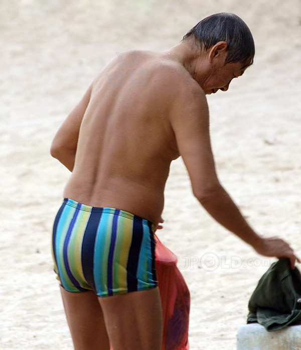 Swimming old man in color striped underwear on beach
