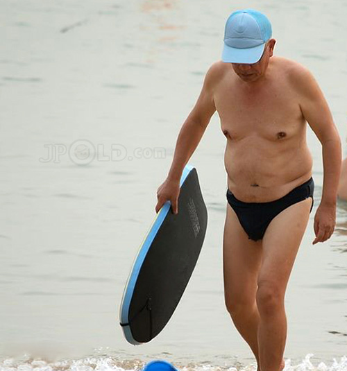 Old daddy wearing a blue cap in black underwear at the sea