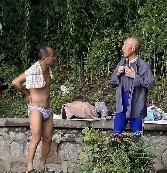 Two swimming old men talking by the lake