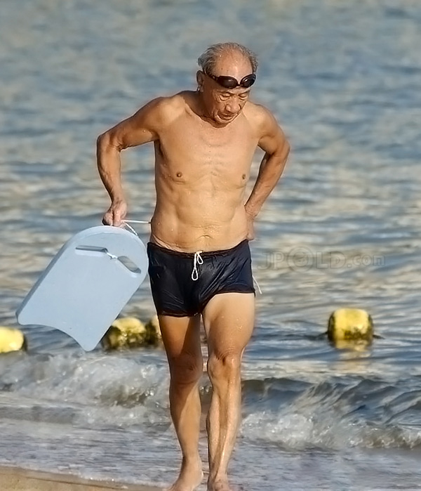 Swimming old man in purple underwear out of water