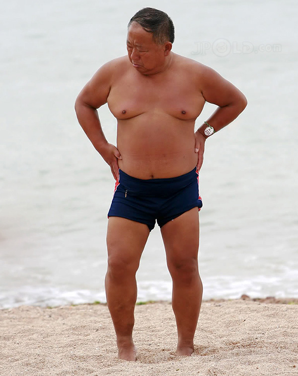 Fat swimming old daddy in blue underwear on the beach
