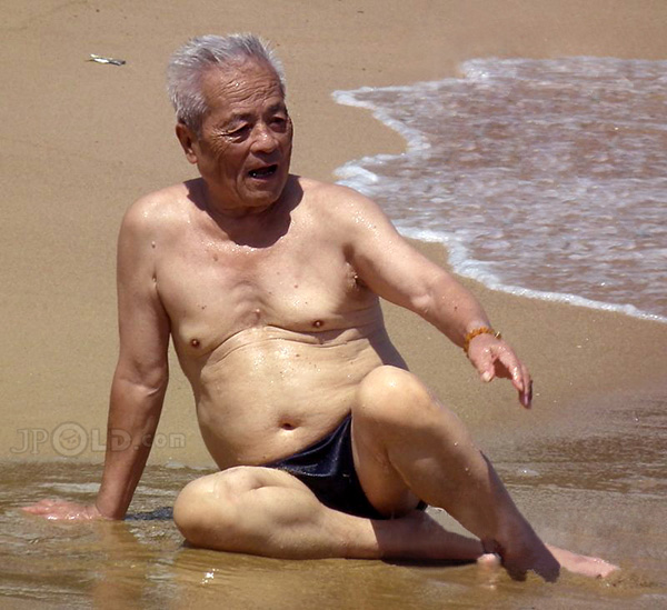 White hair old man in black underwear sitting on beach