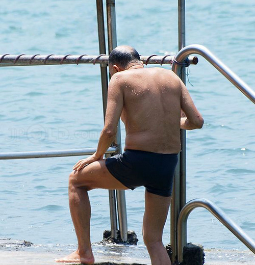 Swimming old man in black underwear pissing at the sea