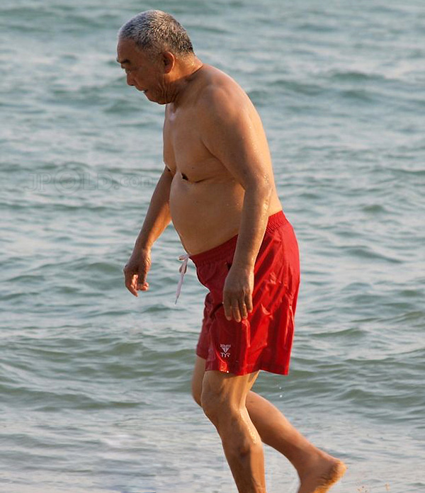 Short white hair old man in red Mid-pants at the sea