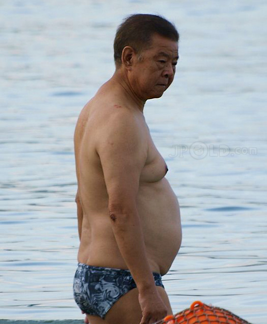 Belly swimming old daddy in blue underwear at the sea