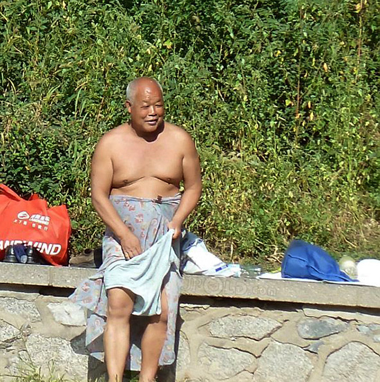 Bald swimming daddy changing his blue underwear by the lake