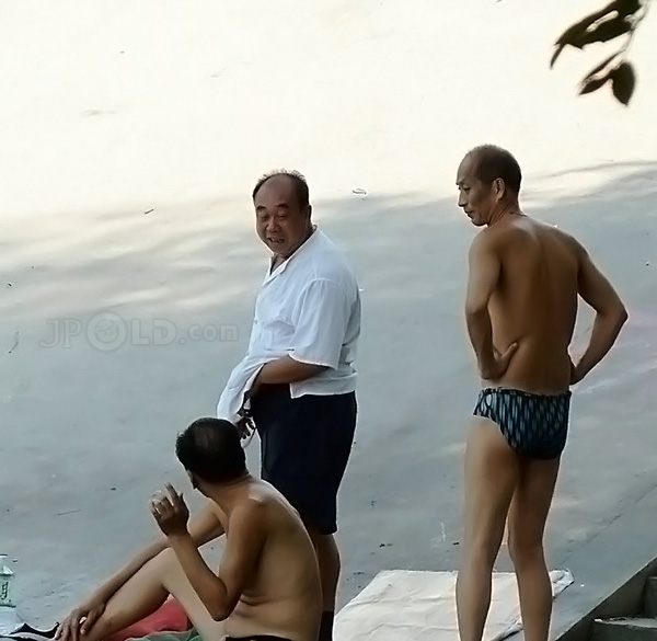Three swimming men by the river