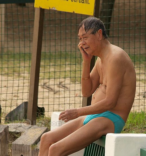 Swimming old man in blue underwear at the sea