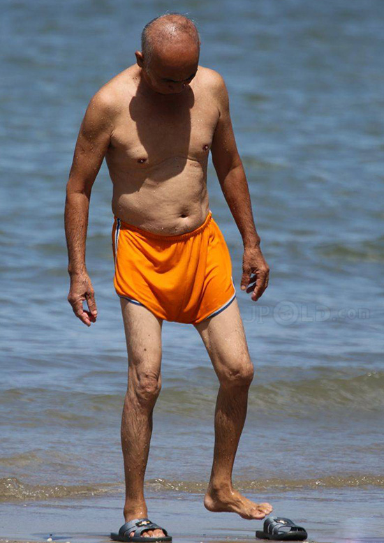 Swimming old daddy in orange underwear at the sea