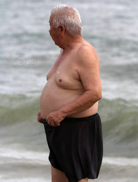 Fat swimming white hair old man in black pants on the beach