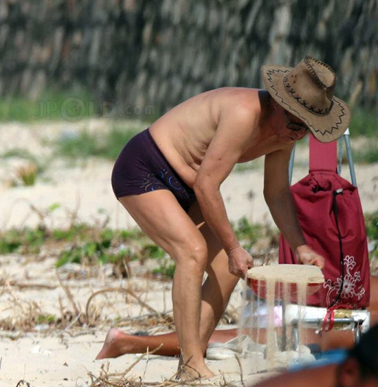 Glasses swimming old man in black underwear playing sand on the beach
