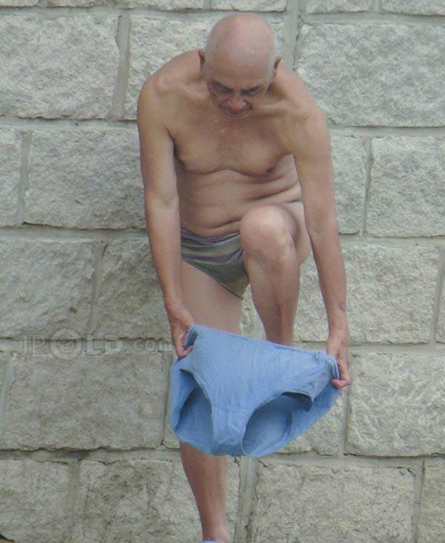 Bald swimming old man put on his blue pants