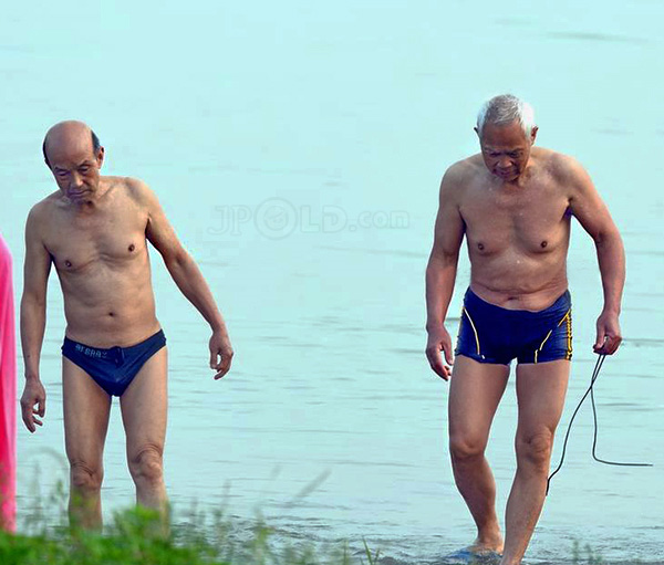 Two swimming old men in blue underwears by the river
