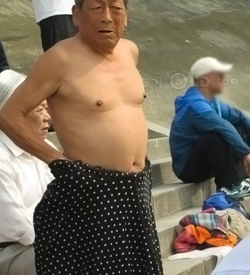 Swimming old daddy changing his pants on the stone stairs