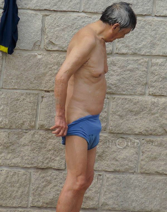 Swimming old man dressing his blue pants