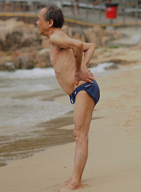 Old man in deep blue underwear at the sea