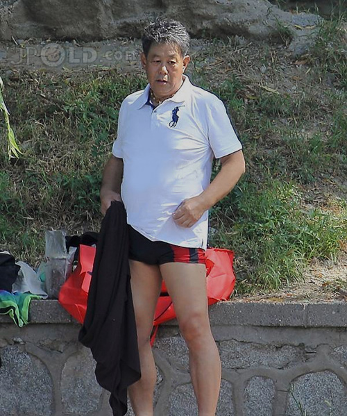 Swimming daddy in black and red pants by the river