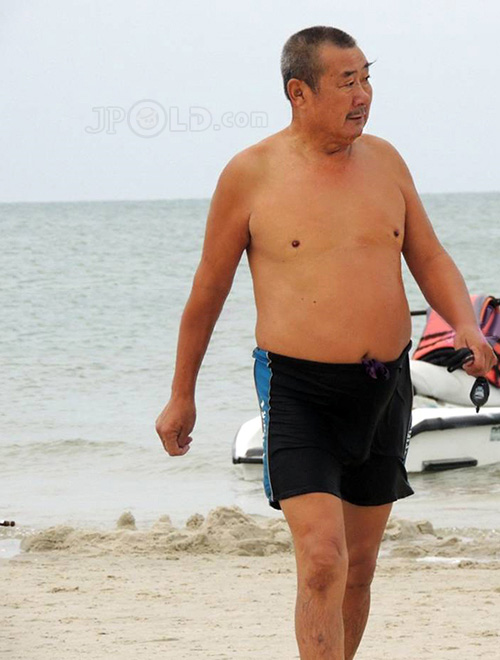 Old uncle in black pants at the sea