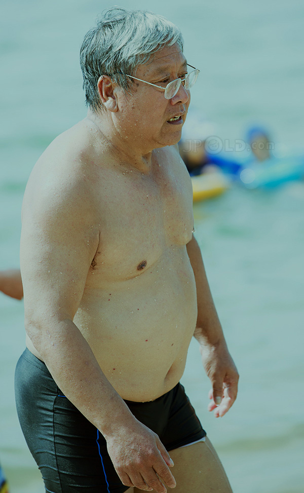 White hair swimming old man in black pants at the sea