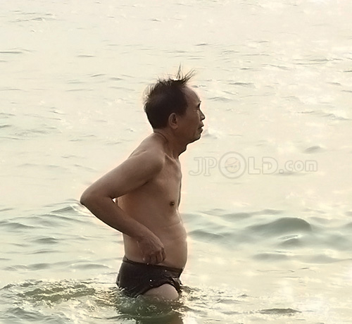 Old man in a black underwear at the sea