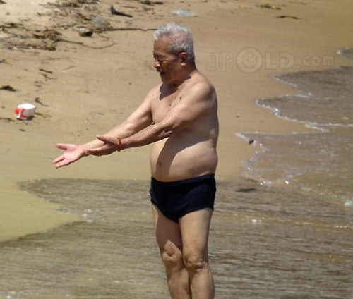 Silver hair swimming old man in black pants at the sea