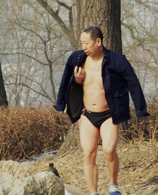 Old daddy in black underwear by the lake in winter