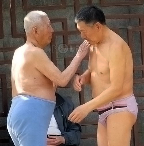 Two swimming old men in pants talking by the lake