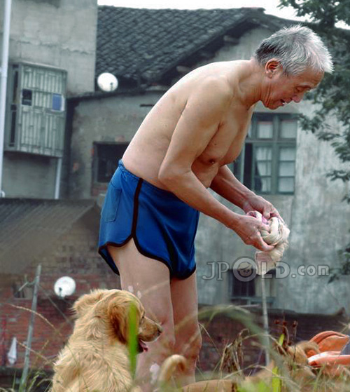 Skinny old man in blue boxer shorts on the field with his dog