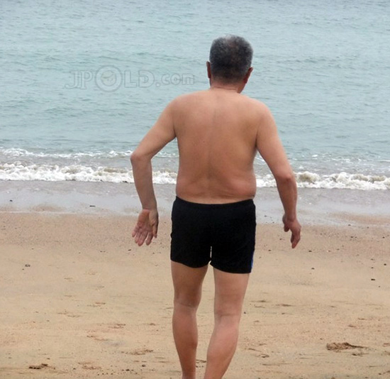 Swimming old daddy in black pants on foot at the sea