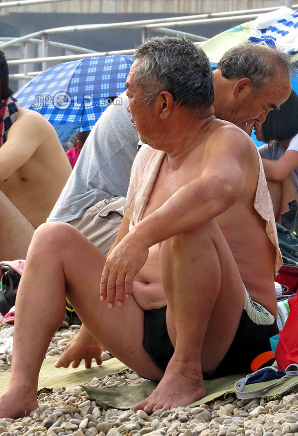 Swimming father in black pants sitting on the bench