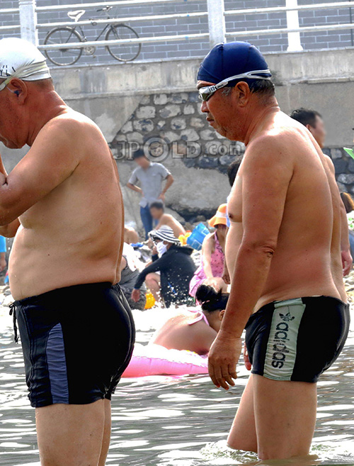 Swimming old men in swimsuits at the sea