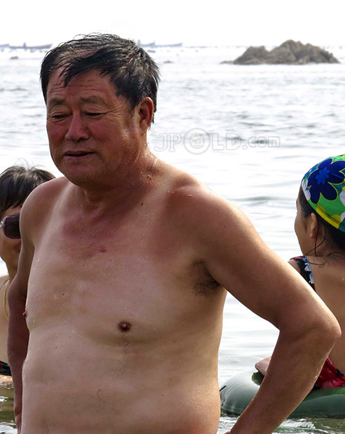 Swimming old daddy in black boxer shorts on the beach